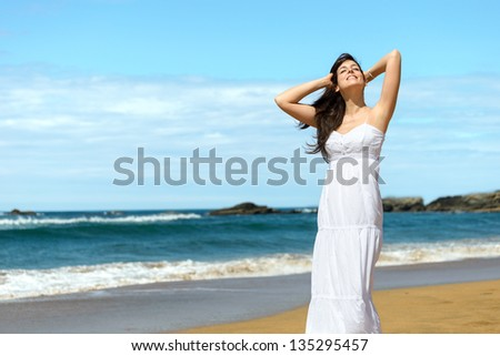 Woman relaxing and enjoying summer vacation on beach. Happy caucasian girl in Playa de Verdicio, Asturias, Spain. Copy space.