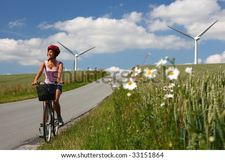 Woman relaxing and enjoying the sun on a bike trip in the countryside of Jutland, Denmark. Wind turbines in the background.