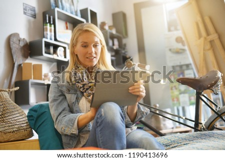 Woman relaxing at coffee shop using digital tablet