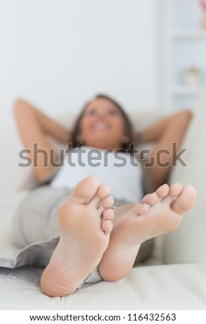 Woman relaxing at home with her feet up on the sofa