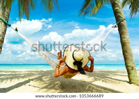 Woman relaxing at the beach on a hammock #1053666689