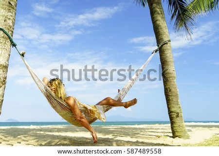 Woman relaxing at the beach on a hammock #587489558