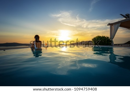 Woman relaxing at the edge of infinity swimming pool at sunset