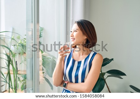 Woman relaxing behind the door/window and holding a cup of tea