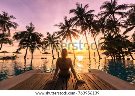 Woman relaxing by the pool in a luxurious beachfront hotel resort at sunset enjoying perfect beach holiday vacation - Shutterstock ID 763956139