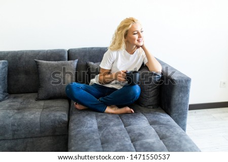 Woman relaxing drinking coffee sitting on a sofa in the living room in a house interior