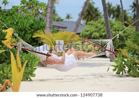 Woman relaxing in a hammock and reading a book on a beach in Maldives