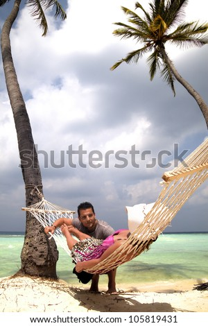 Woman relaxing in a hammock strung between palm trees on a tropical beach chatting to a handsome young man