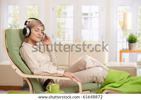 Woman relaxing in armchair at home enjoying music in headphones, smiling.? - stock photo