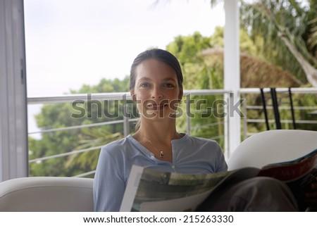 Woman relaxing in armchair near balcony, reading magazine, smiling, portrait