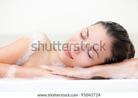 woman relaxing in bath with serene smile and closed eyes with bath foam. Beautiful young multiracial Caucasian / Asian Chinese female model.
