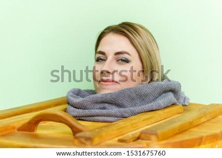 Woman relaxing in cedar spa barrel, body rejuvenation and relax sauna