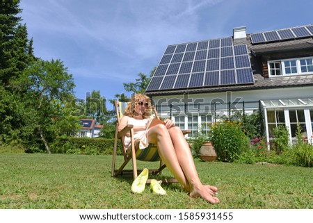 Woman relaxing in garden of solar paneled house