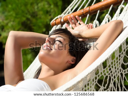 Woman relaxing in hammock for siesta outdoors. Beautiful woman and lying down and relax in garden on summer. .