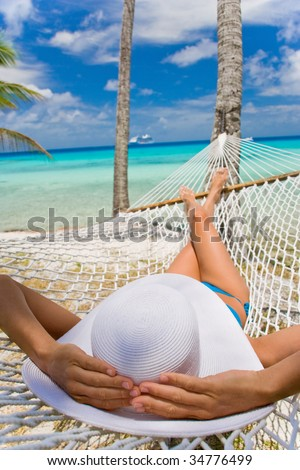 woman relaxing in hammock near tropical resort