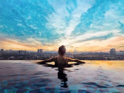 Woman relaxing in infinity pool with city view. Relaxing vacation.