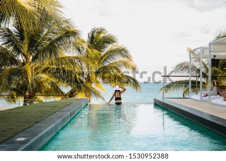 Woman relaxing in infinity swimming pool looking at view. Luxury resort. Beautiful destination summer vactions. Back view of traveller girl in beach hat and white bikini relax on Mexico.