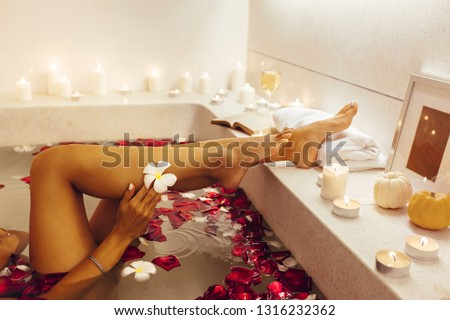 Woman relaxing in luxury bath decorated with candles and petals. Organic skin care in tropical spa resort. Closeup photo of female legs with flower.