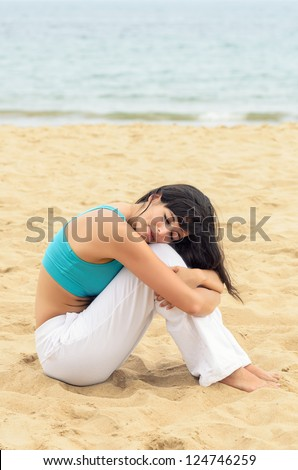 Woman relaxing in peace sitting on sand beach near the sea. Serene woman tranquility on summer morning. Copyspace.
