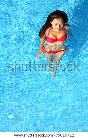 Woman relaxing in swimming pool. Beautiful gorgeous young bikini model bathing in blue swimming pool on resort during holiday. Pretty multiracial Asian / Caucasian woman in red bikini.