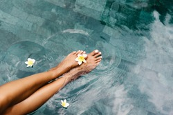Woman relaxing in swimming pool in Bali luxury resort. Foot spa and skin care lifestyle. Top view photo of legs closeup.