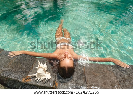 Woman relaxing in swimming-pool. lying on the back with closed eyes. Relax and spa concept