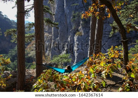 Woman relaxing in the turquoise hammock in a wood. Concept of relaxation and meditation