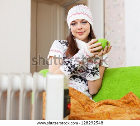 woman relaxing near oil heater at home with cup in winter