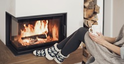 Woman relaxing near the fireplace, female holding with cup of tea, enjoying life at home. Girl wearing warm clothes. Winter fun, lifestyle, leisure, lockdown, holidays, vacations, Christmas, New Year