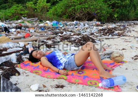 Woman relaxing on a beach very polluted by plastic pollution, Thailand #1461142268