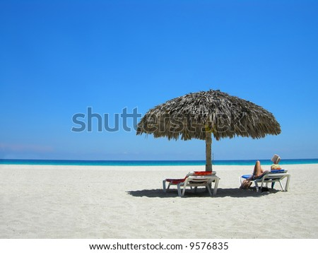 woman relaxing on a lounger reading a book at a tropical beach
