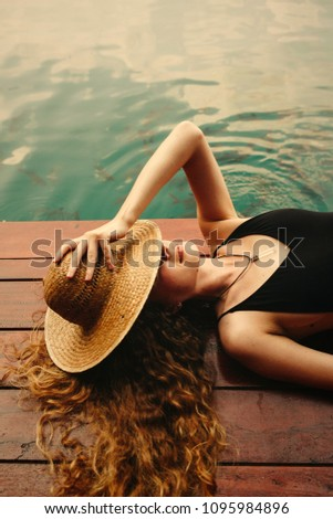 Woman relaxing on a wooden jetty #1095984896