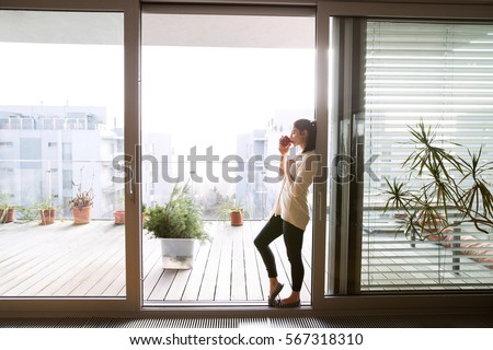 Woman relaxing on balcony holding cup of coffee or tea #567318310