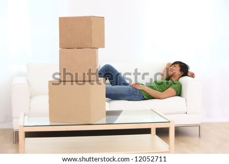 Woman relaxing on couch with boxes in foreground