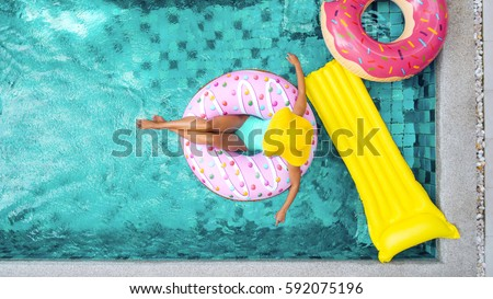 Woman relaxing on donut lilo in the pool at private villa. Inflatable ring and mattress. Summer holiday idyllic. High view from above. #592075196