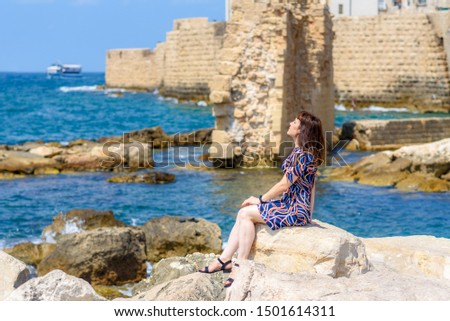 Woman relaxing on sea beach, hot sunny day. Middle aged woman relaxing on sea beach, hot sunny day.