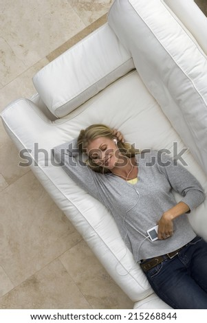 Woman relaxing on sofa at home, listening to MP3 player, smiling, portrait, overhead view