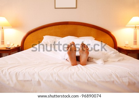 Woman relaxing on soft big bed with white sheets; focus on feet