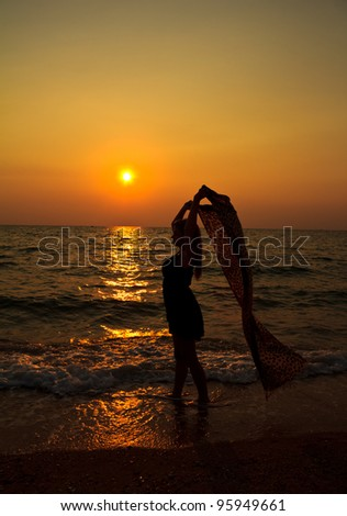 Woman relaxing on the beach at sunset