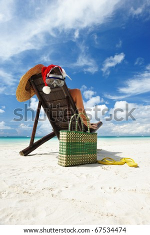 Woman relaxing on the beach in santa's hat