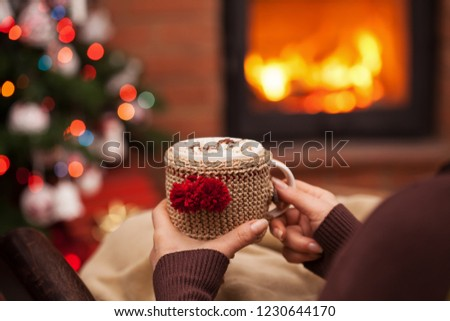 Woman relaxing with a cup of hot chocolate sitting in an armchair by the fireplace and christmas tree - closeup on winter evening relaxation detail #1230644170