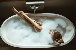 Woman relaxing with pleasure in foam bath with bubbles and touching her smooth leg skin in modern hotel dark bathroom, top view