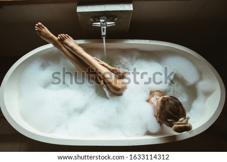 Woman relaxing with pleasure in foam bath with bubbles and touching her smooth leg skin in modern hotel dark bathroom, top view Foto d'archivio ©