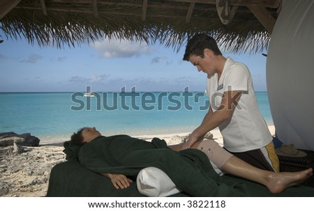 woman relaxing with professional massage at resort by the sea