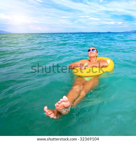 Woman relaxing with yellow tube in tropical lagoon