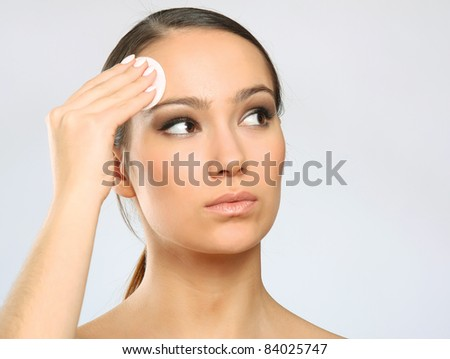 Woman removing makeup with cleansing pads isolated on grey background