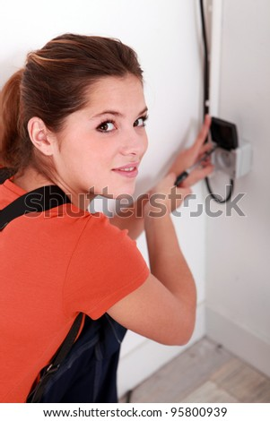 Woman repairing an electrical outlet