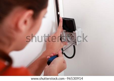 Woman repairing electrical socket