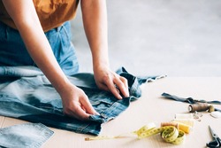 Woman repairs sews reuses fabric from old denim clothes economical reuse. DIY Hobby Reuse Recycling