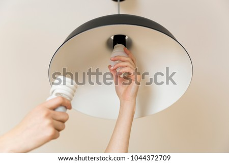 Woman replacing light bulb at home. Power save LED lamp changing #1044372709